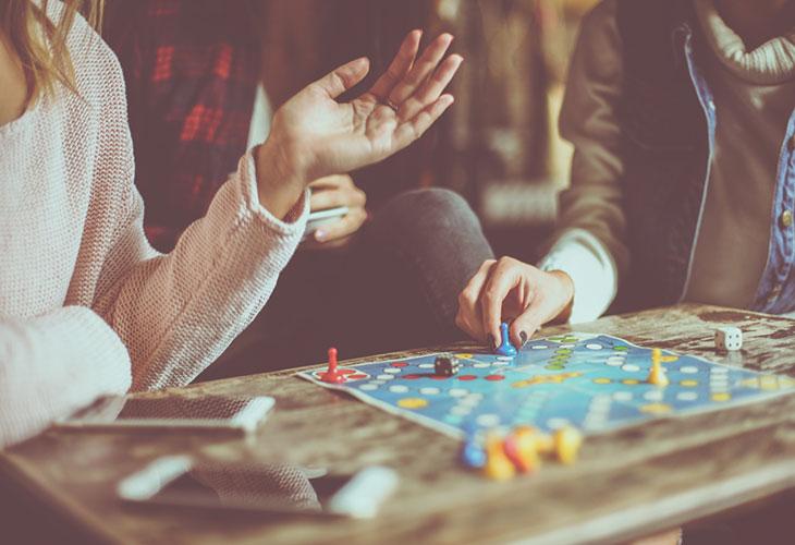 Lautapelit tarjoavat kivaa ajanvietettä. Kuvassa ystävykset pelaavat.