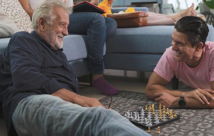 Miten luoda syvempi suhde vanhempiin tai sukulaisiin aikuisiällä? Kuvassa isä ja poika pelaavat shakkia.