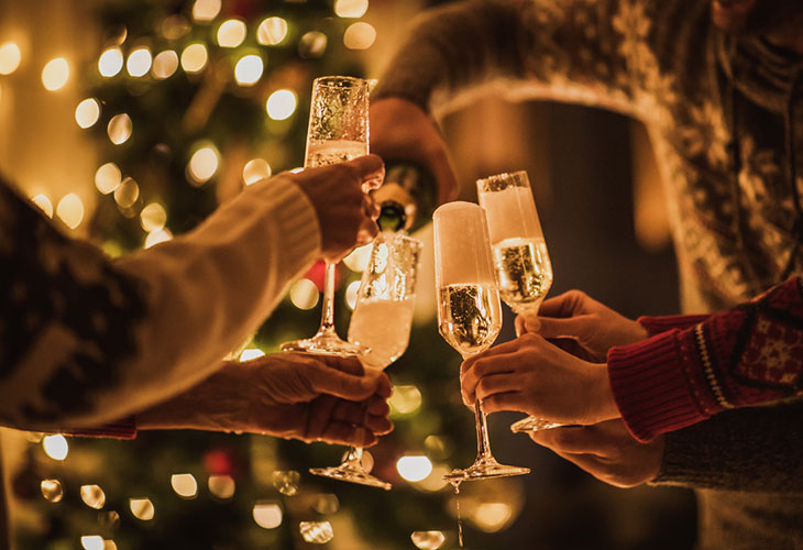 Alkoholinkäyttö kuuluu monen suomalaisen jouluun. Kuvassa joukko ihmisiä pitelee kuohuviinilaseja.