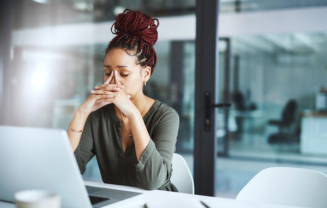 Nainen istuu tietokoneella pää painettuna käsiinsä.