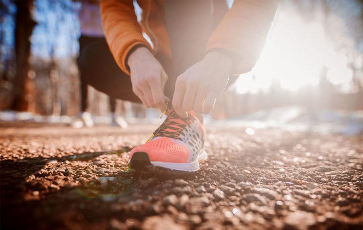 Ihminen sitomassa treenikenkää lenkkipolulla. Parhaimmat treenikengät ovat sellaiset, joilla alustan tuntee, eikä kenkiin ole lisätty erityisiä tukia, ellei jaloissa ole erityistä tuen tarvetta.