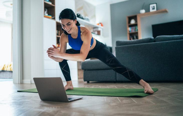 Nainen venyttelee joogamatolla kannettavan tietokoneen edessä. Tämä pakaratreeni kotona saa taatusti hien pintaan.