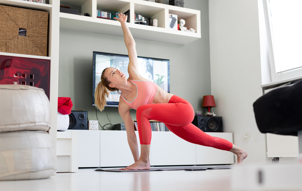 Liikkuvuusharjoittelu – kuvassa nainen venyttelee olohuoneessa joogamatolla.