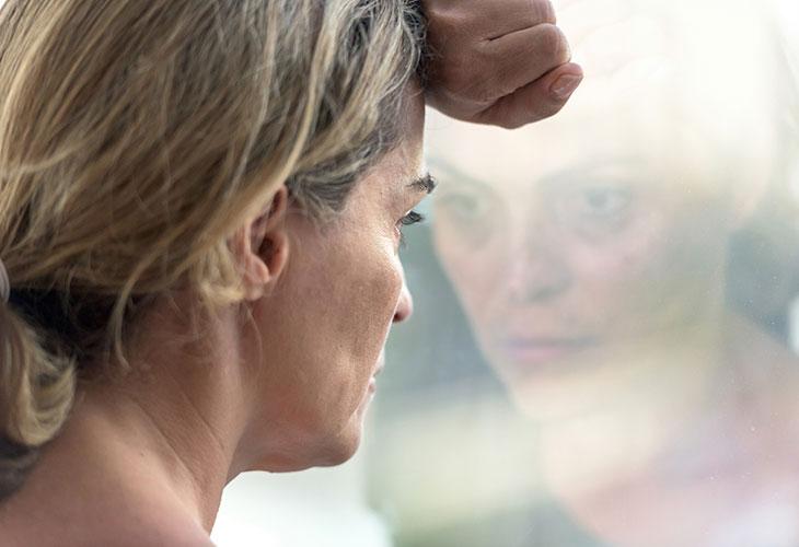 On mahdollista, että e-pillerit aiheuttavat vakaviakin mielialaoireita. Kuvassa nainen katsoo ikkunasta ulos.