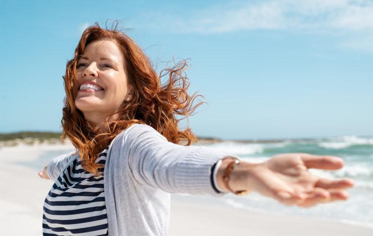 Keski-ikäinen nainen iloitsemassa rannalla. Vaatimattomuus on hyvä piirre silloin, jos se kumpuaa siitä, että on tyytyväinen siihen mitä itsellä on.