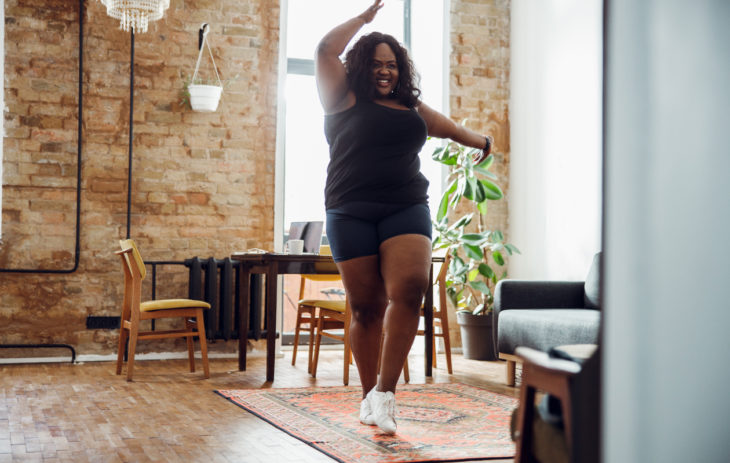 Nainen liikkuu olohuoneessa nauraen. Syketreeni onnistuu pienissäkin sisätiloissa.