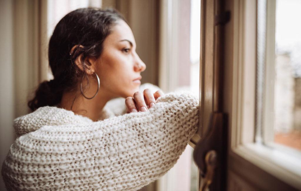 Kuolemanpelko voi rajoittaa ihmisen toimintakykyä. Kuvassa henkilö katsoo ikkunasta ulos.