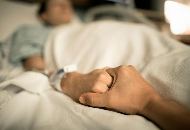 Kuolemanpelko nostaa päätä esimerkiksi sairastumisen myötä. Kuvassa sairaalassa oleva henkilö pitää toista ihmistä kädestä kiinni.