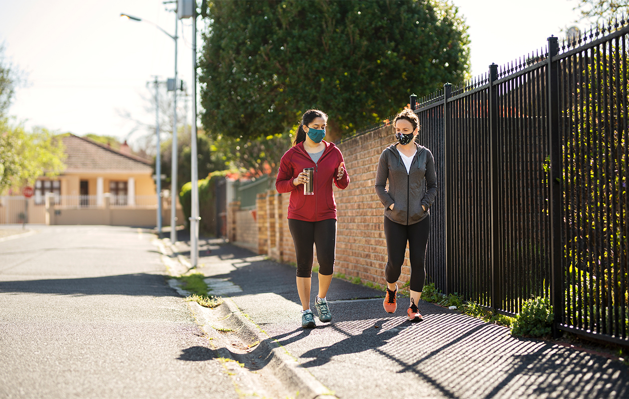 Kaksi naista kävelyllä ulkona kasvomaskit päällä.