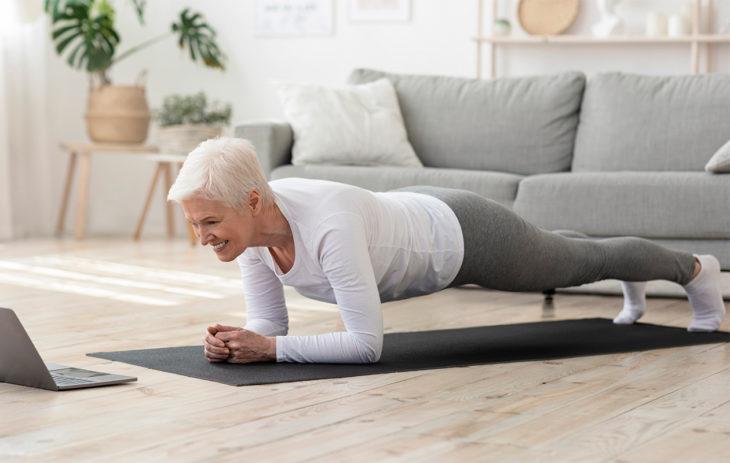 Vanhempi nainen lankuttaa kotinsa lattialla hymyillen. Lihaskuntotreeni kotona on hyvä tapa urheilla – vaikka kesken etätyöpäivän.
