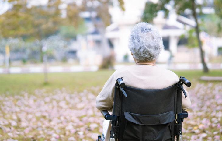 Iäkäs nainen istuu pyörätuolissa pihalla, selkä kameraan päin. ALS-tauti on yleensä keski-ikäisten tauti, mutta siihen voi sairastua myös nuorempana.