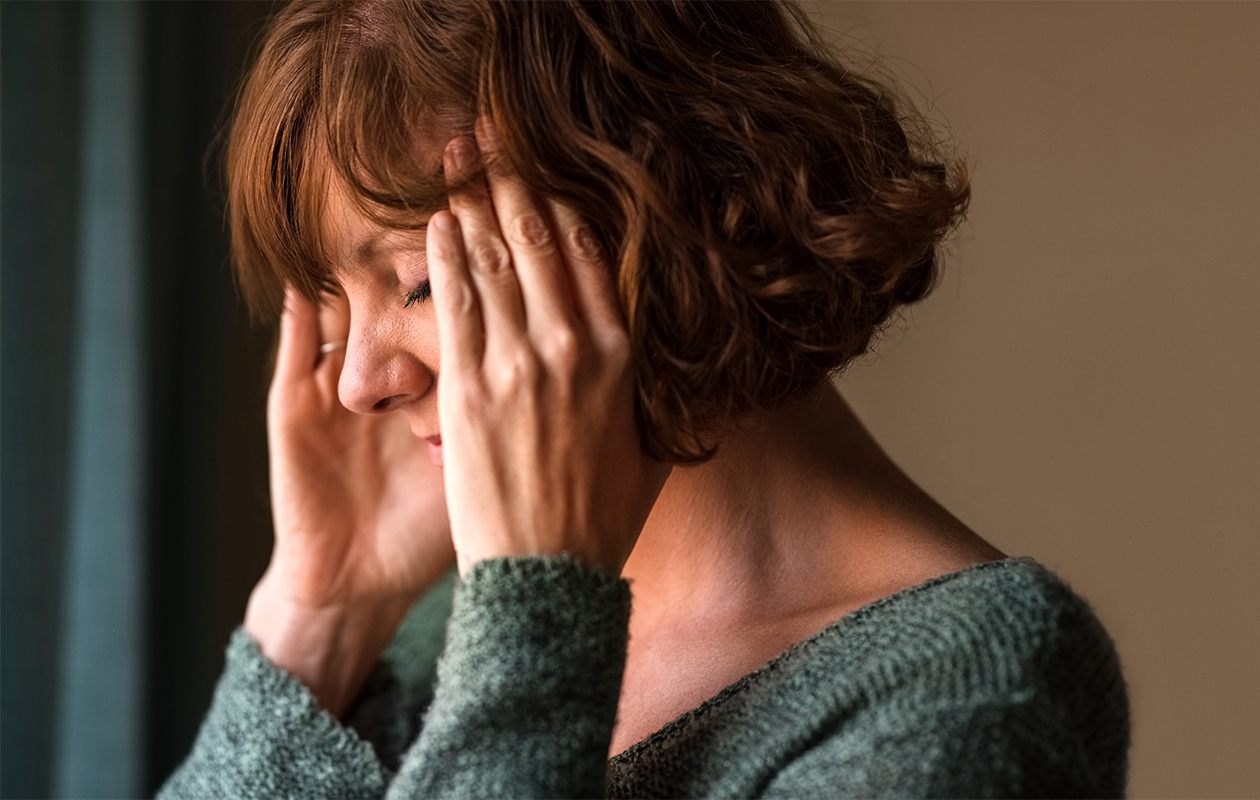 Keski-ikäinen nainen pitelee ohimoa ahdistuneen oloisena.