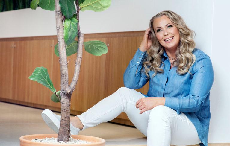 Johanna Pakonen istuu ja nauraa.