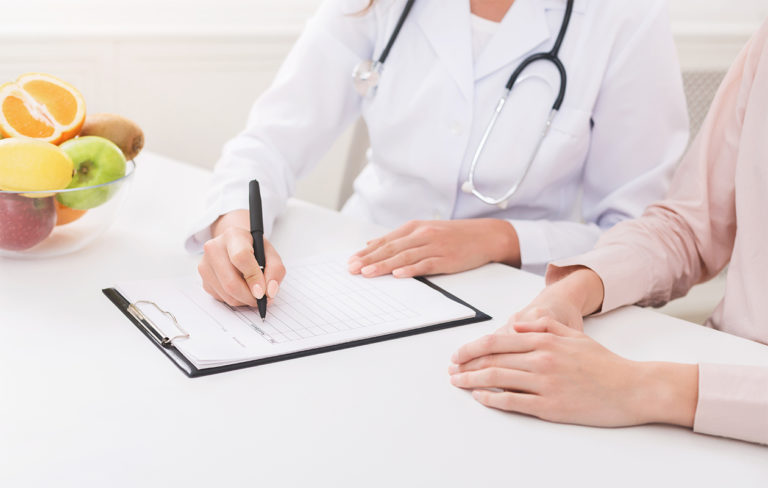 Lääkäri kirjoittaa lomakkeelle, vieressä potilaan kädet pöydällä.