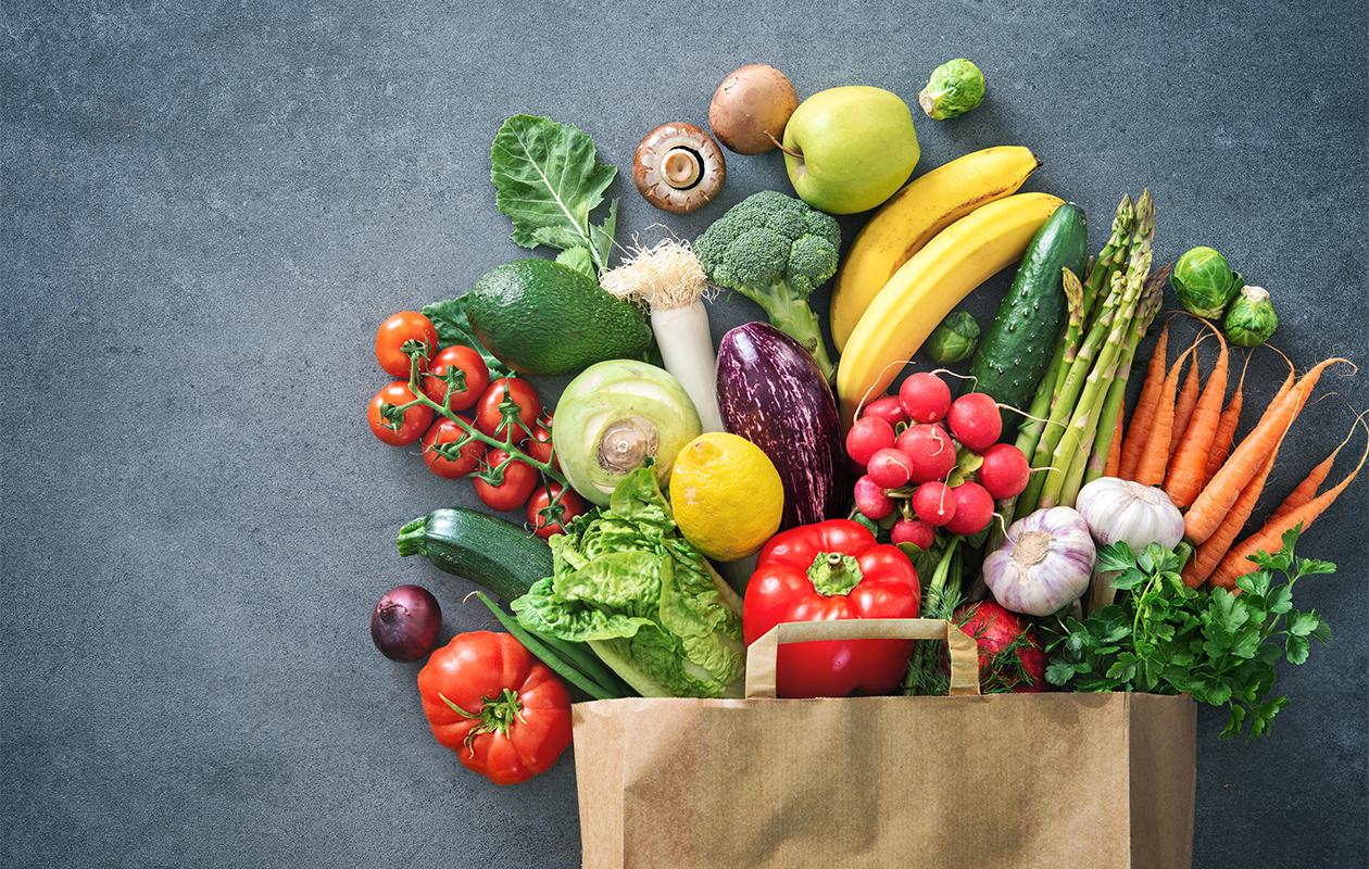 Kuvassa hedelmiä ja kasviksia tursuaa ulos paperikassista.