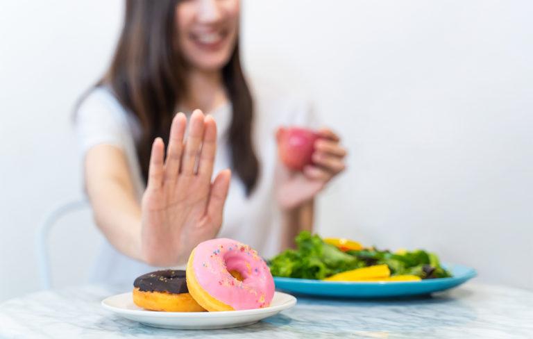 """Etualalla kaksi donitsia, takana sumeana nainen näyttämässä """"stop""""-kättä herkuille."""