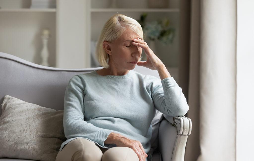 Nainen istuu sohvalla ja nojaa väsyneenä käteen.