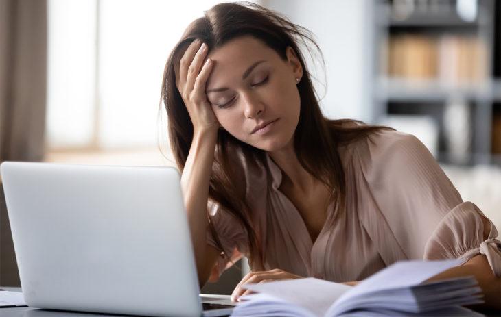 Nuori nainen istuu väsyneenä silmät kiinni tietokoneen edessä. Krooninen väsymysoireyhtymä eli CFS voi olla jopa niin vaikea, että haittaa normaalia elämää.