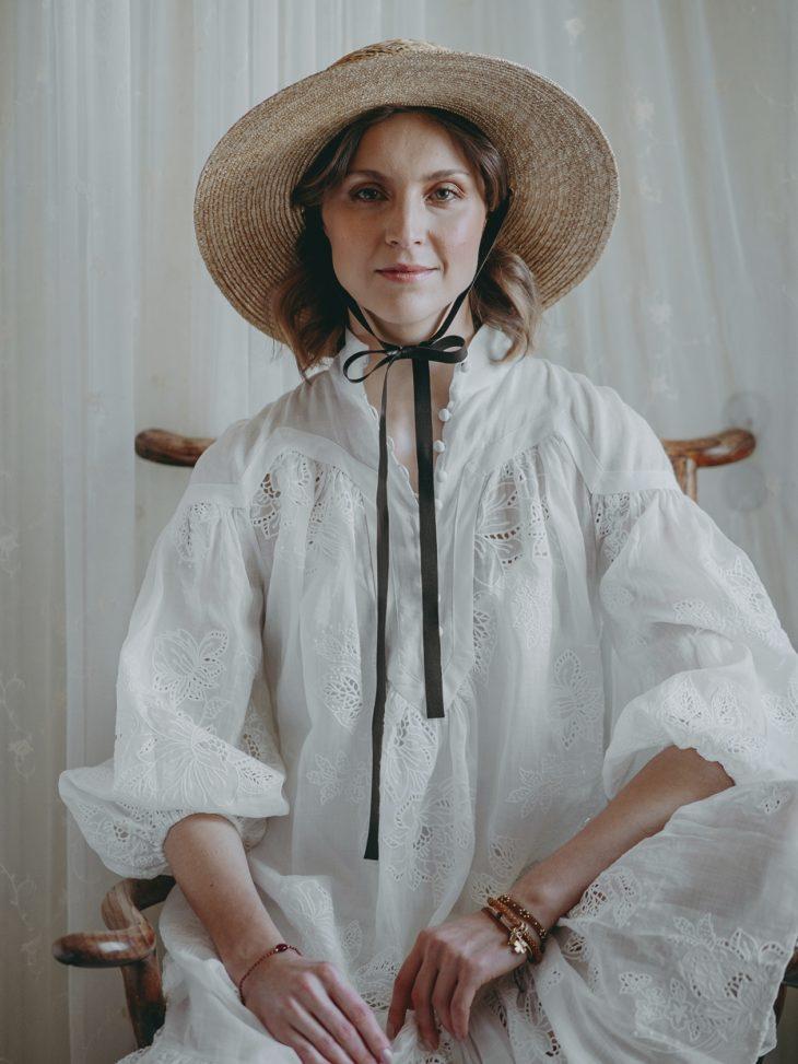 Valkoinen pitsikoristeinen mekko 1180 e, Zimmermann. Olkihattu 149 e, KN Kati Niemi.
