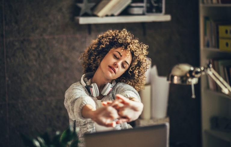 Tauot työaikana on tärkeitä. Kuvassa nainen venyttelee työpöydän ääressä.