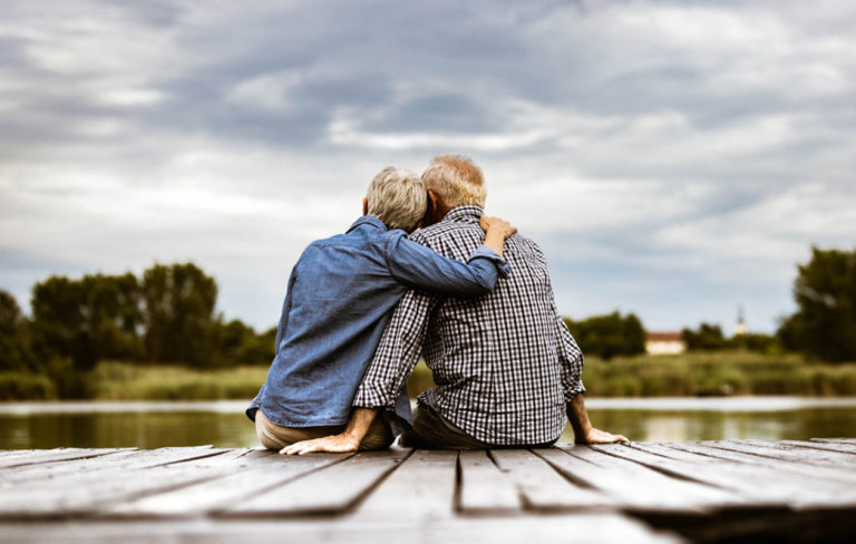 Politiikka on parisuhteessa rakentava keskustelunaihe. Kuvassa pari istuu lähekkäin laiturilla.