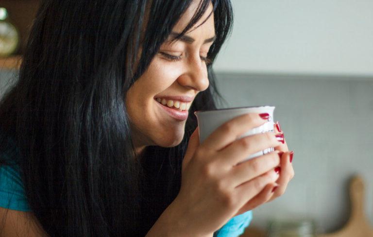 Keltaiset hampaat johtuvat monesta syystä, kuten kahvista. Kuvassa nainen juo kahvia.