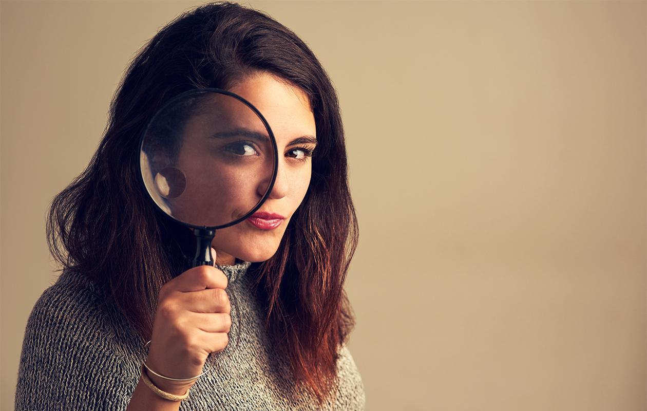 Nainen katsoo kameraan suurennuslasin läpi.