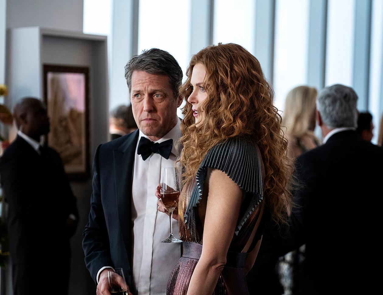 Hugh Grantin ja Nicole Kidmanin hahmot seisovat keskellä salia seurapiirijuhlissa.