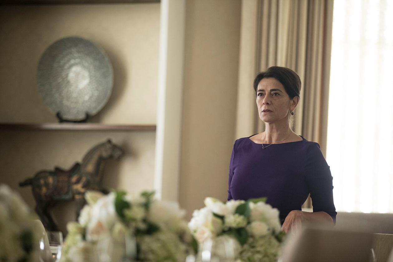 Kuvassa Successions-sarjan naispuolinen hahmo seisoo kukkakimppujen takana.