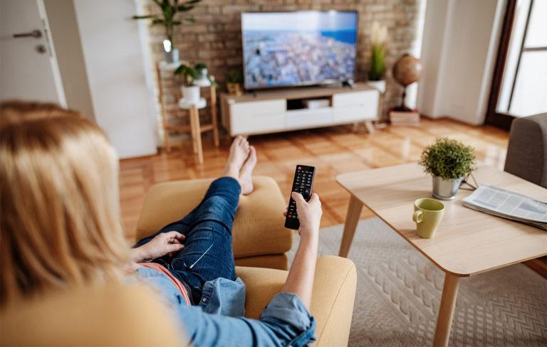 Naishenkilö katsoo televisiota ja osoittaa sitä kaukosäätimellä.