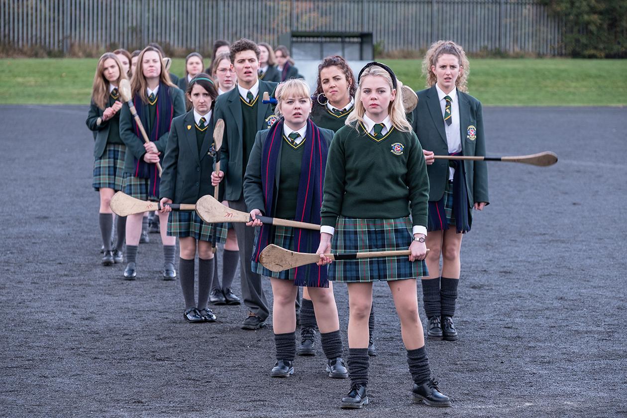 Kuvassa Derry Girls-sarjan hahmot seisovat pelikentällä.
