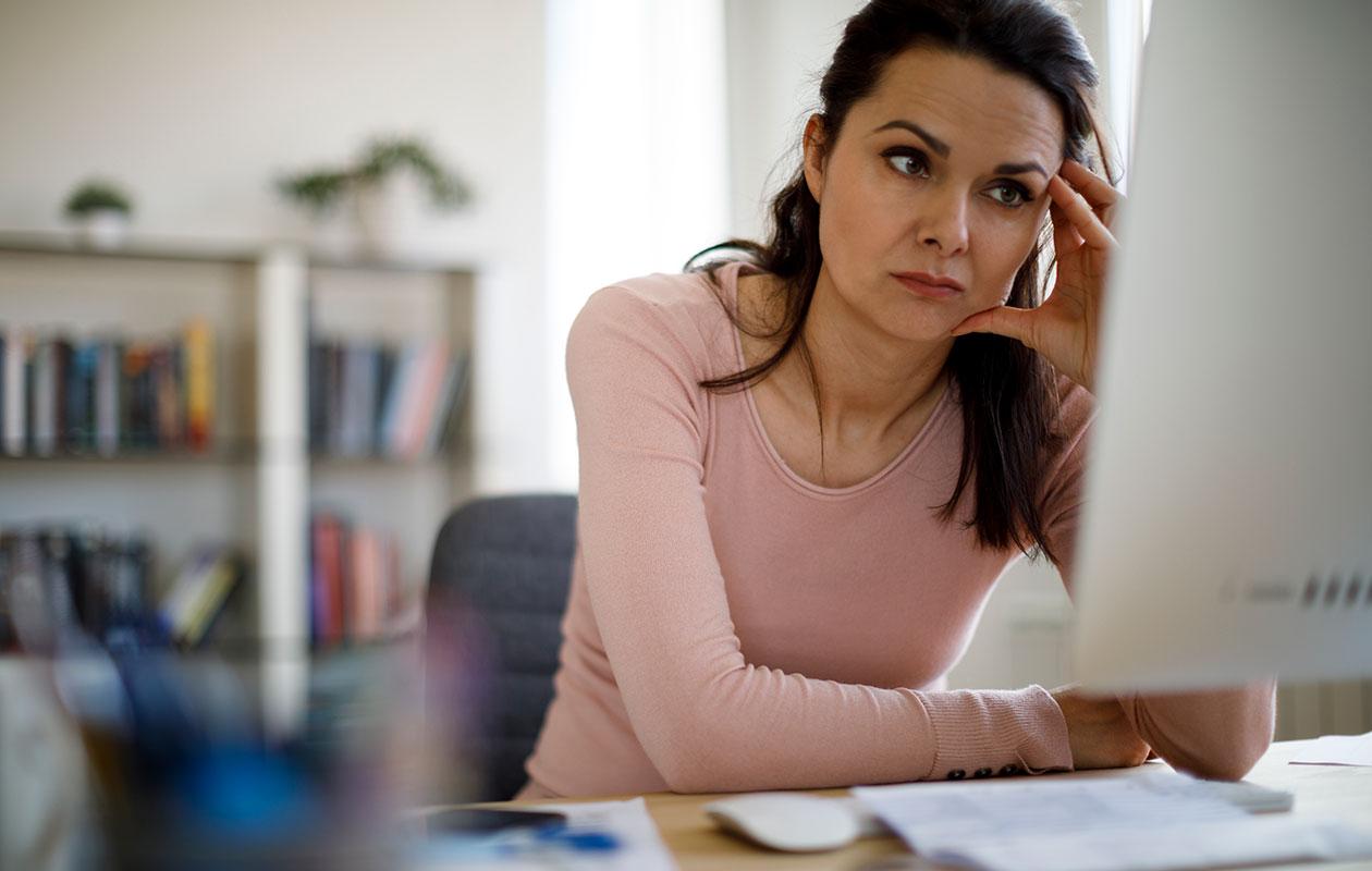 Tyytymättömyys työhön – kuvassa nainen katsoo väsyneenä tietokoneen näyttöä.
