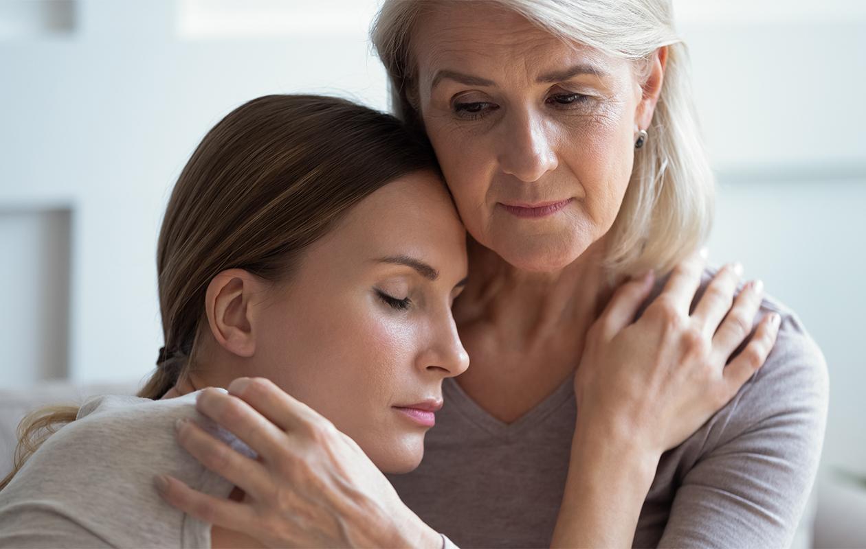 Vanhempi nainen pitelee lohduttavasti nuorempaa naishenkilöä.