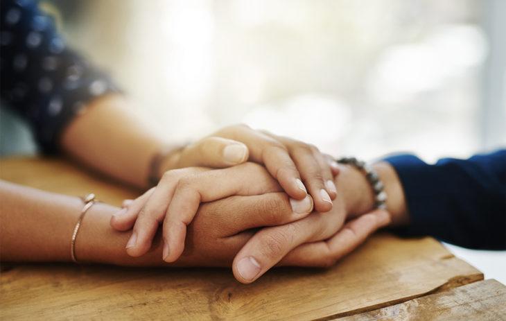 Kaksi ihmistä pitelevät hellästi toisiaan kädestä. Itsemyötätunto auttaa olemaan vaikeissa tilanteissa itsensä puolella, ei itseään vastaan.