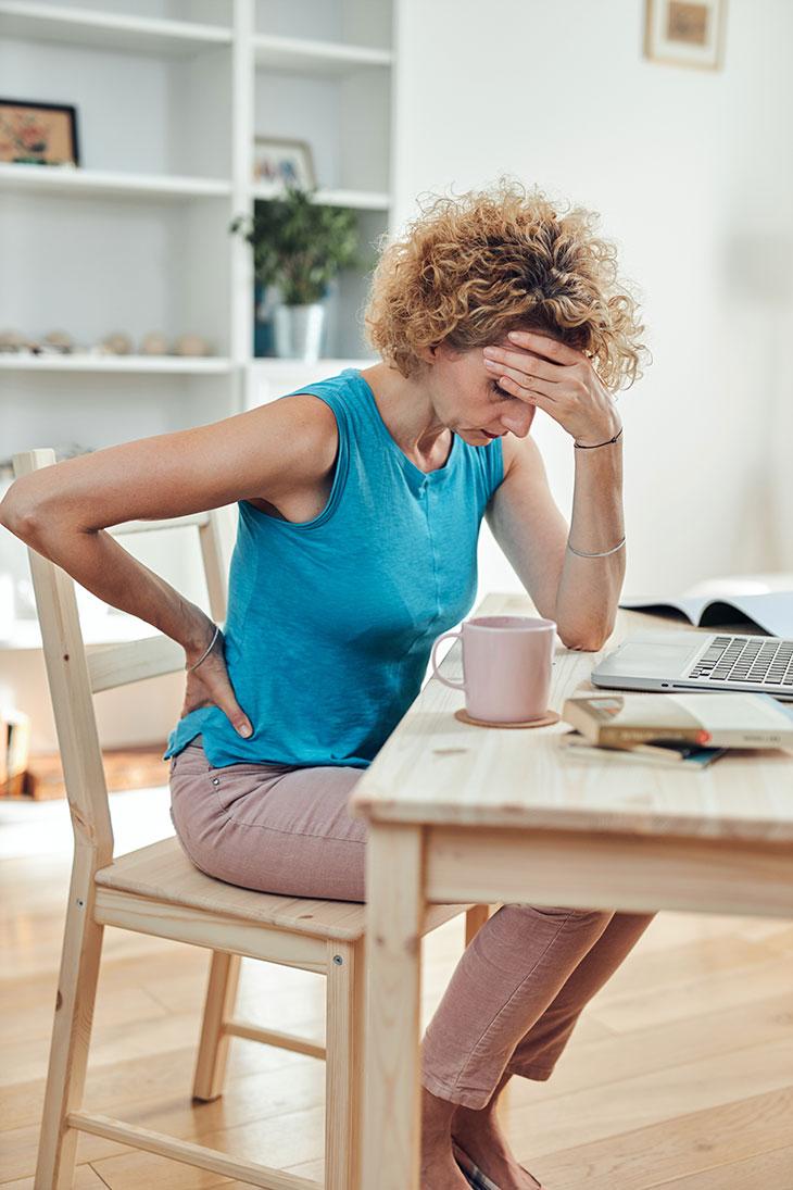Tyytymättömyys työhön – kuvassa nainen katsoo väsyneenä työpöytäänsä.