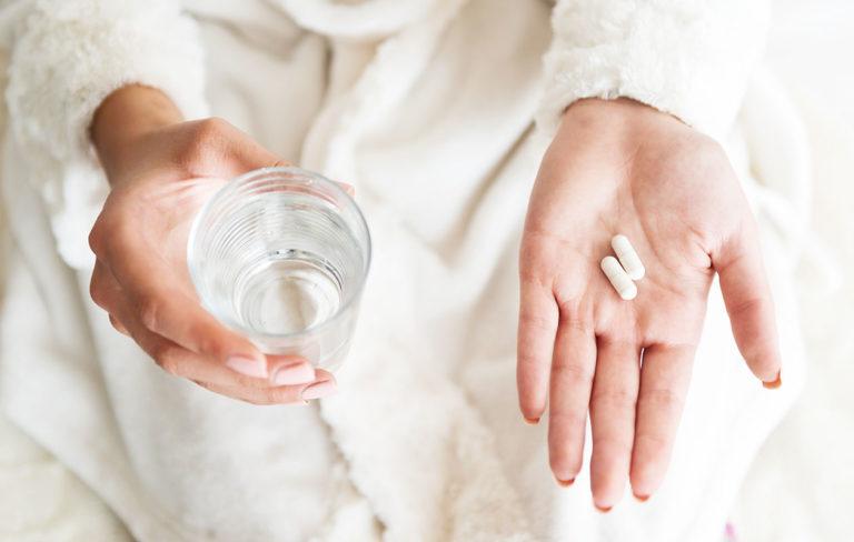 Nainen ottaa lääkkeet veden kanssa.