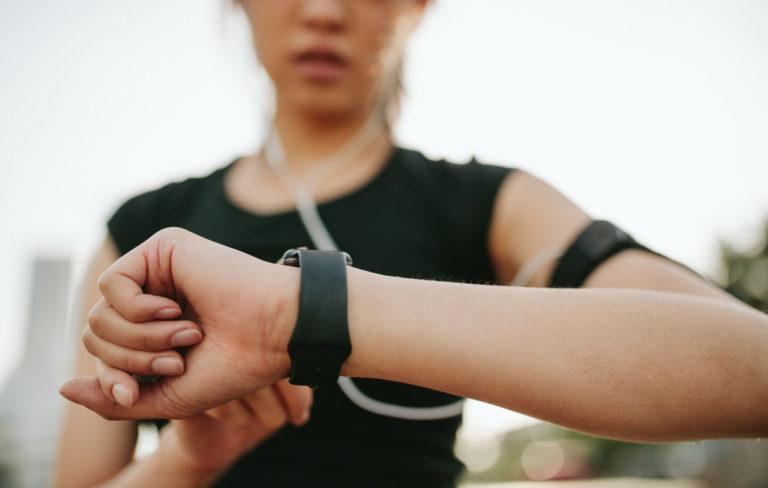 Sitkeä ihottuma ranteessa voi johtua kellosta. Kuvassa nainen katsoo urheilukelloaan.