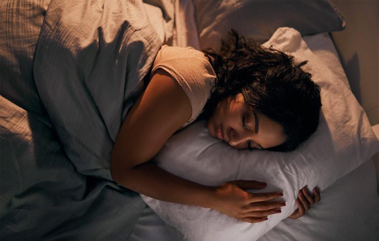 Nainen nukkumassa sängyssä levollisen näköisenä.