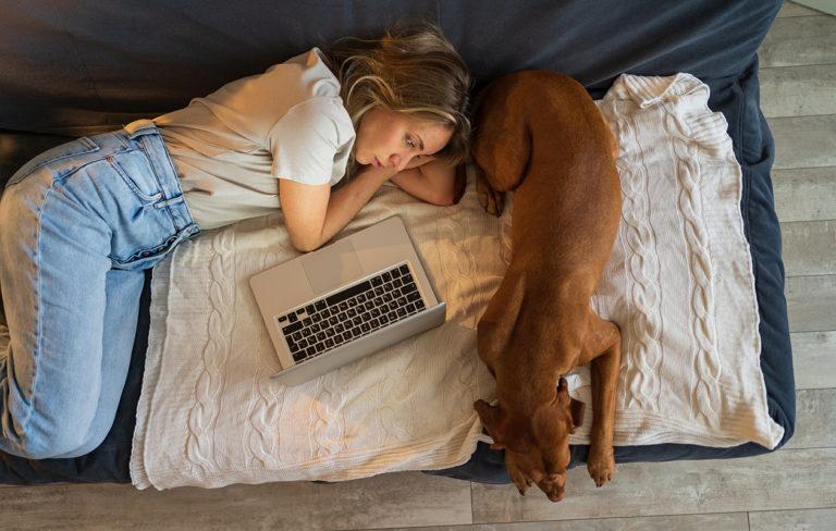 Naisten ADHD heijastuu usein laajalle elämän eri osa-alueisiin. Kuvassa nainen makaa sohvalla koiran ja tietokoneen kanssa.
