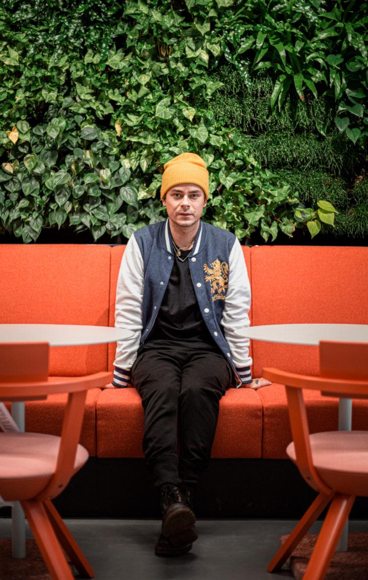 Niko Saarinen istuu penkillä ja katsoo kameraan vakavana.