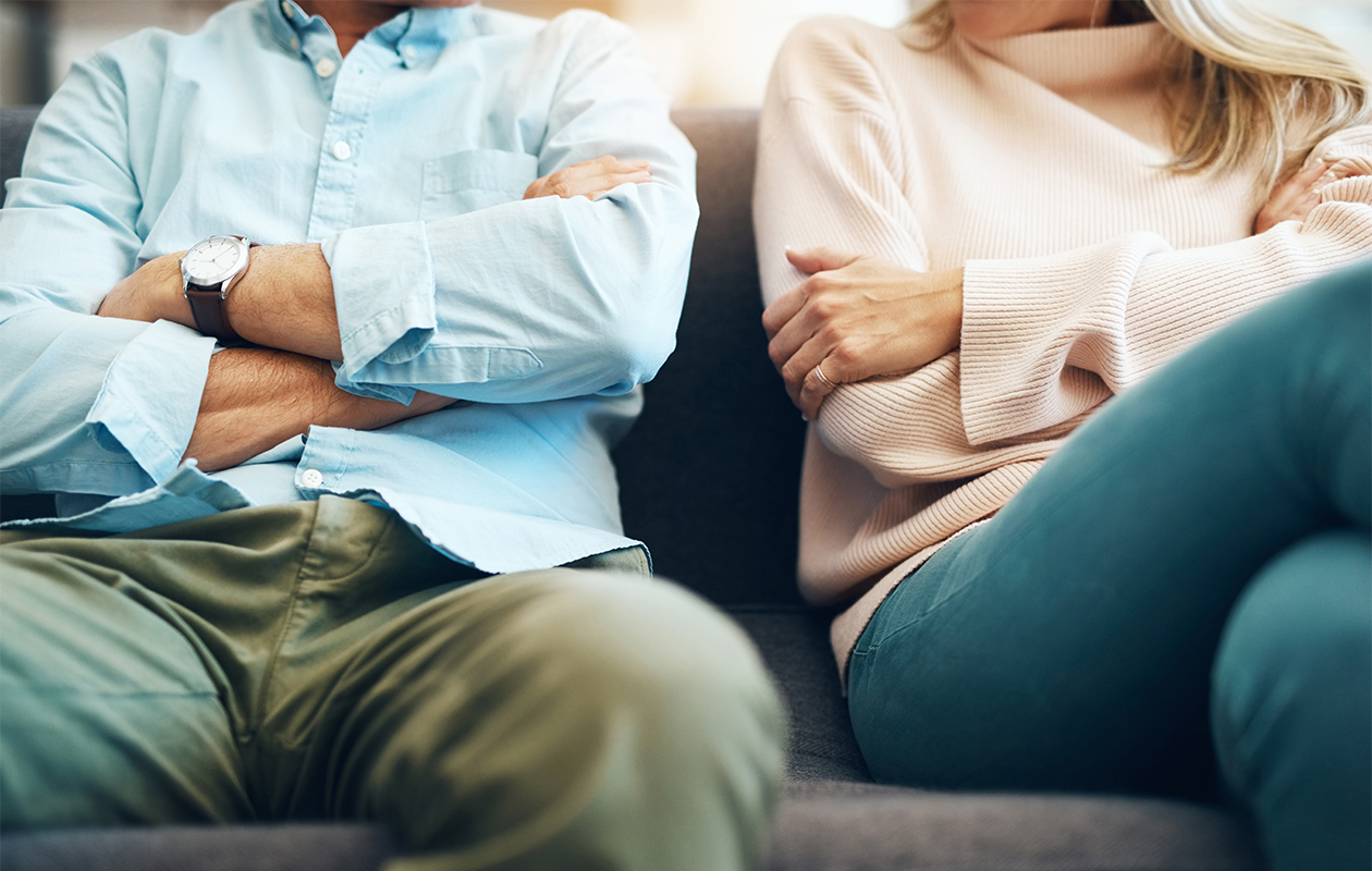 Kaksi ihmistä istuu sohvalla kädet puuskassa.