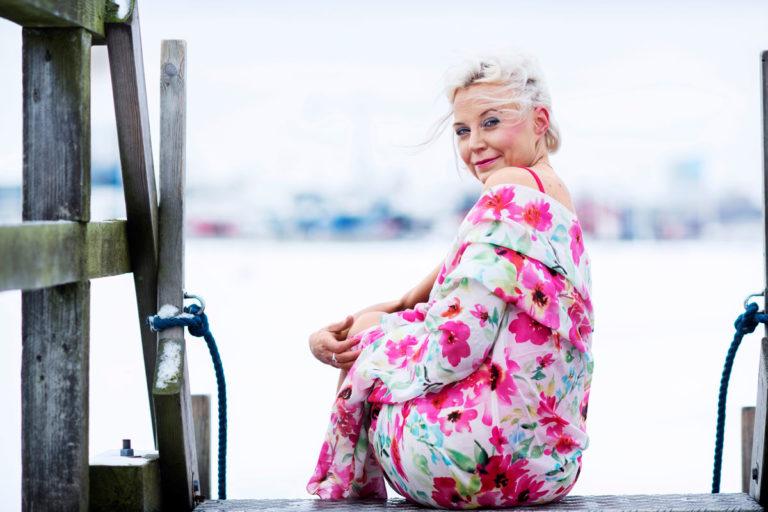 Tutkija Hanna Wass istuu laiturilla Helsingin Uunisaaressa.