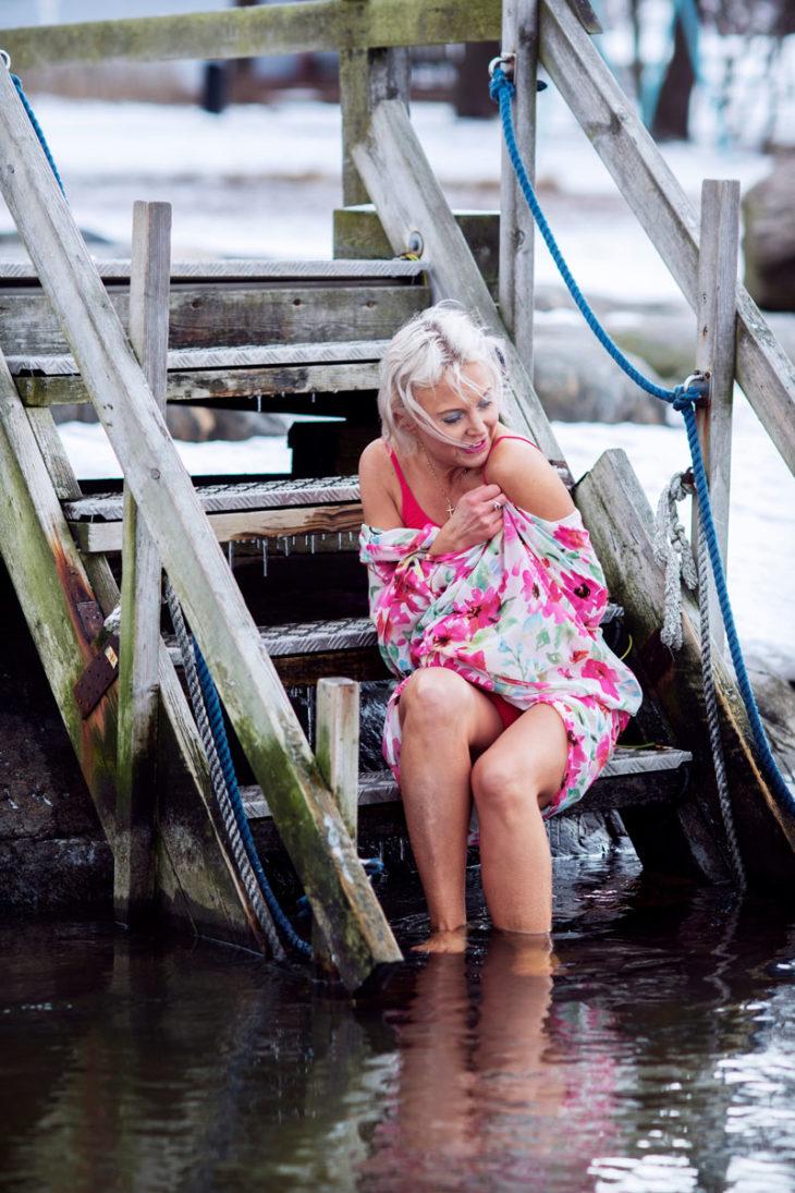 Tutkija Hanna Wass istuu Uunisaaren laiturilla pyyhe päällään.