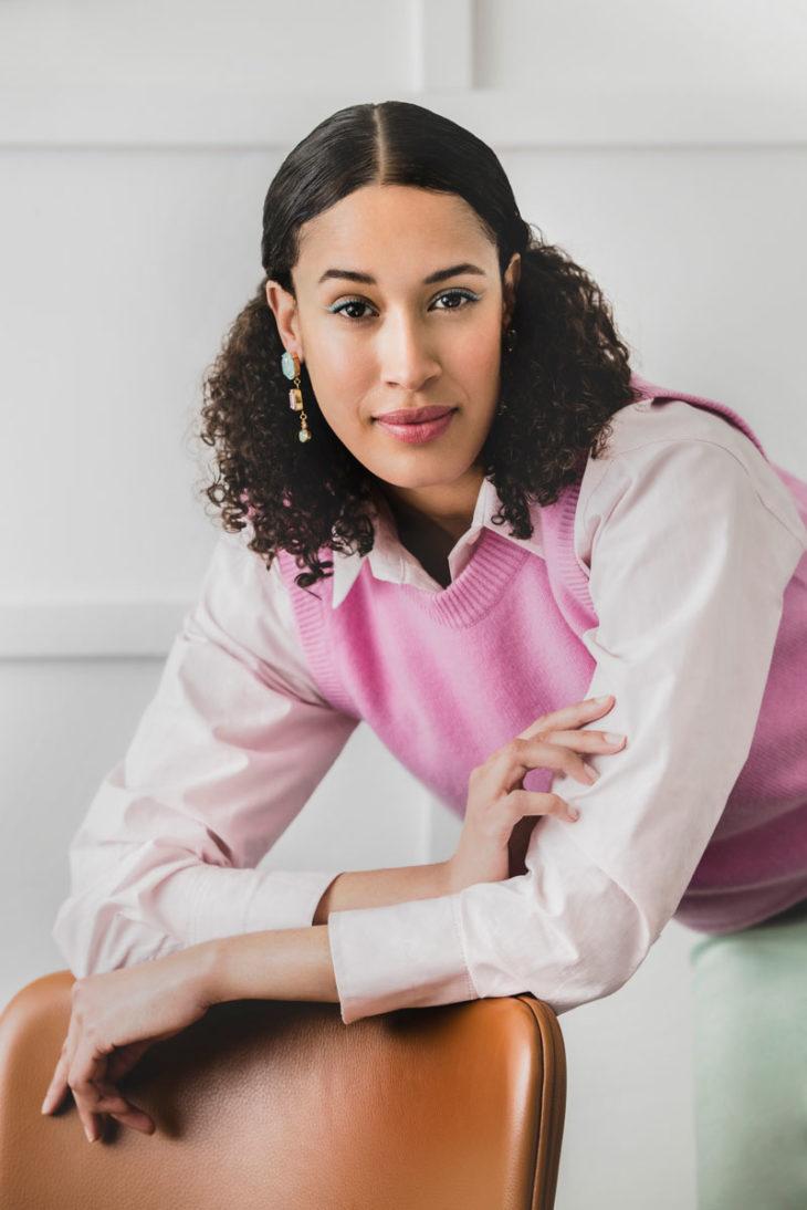 Naisen yllä on paitapusero ja vaaleanpunainen liivi.