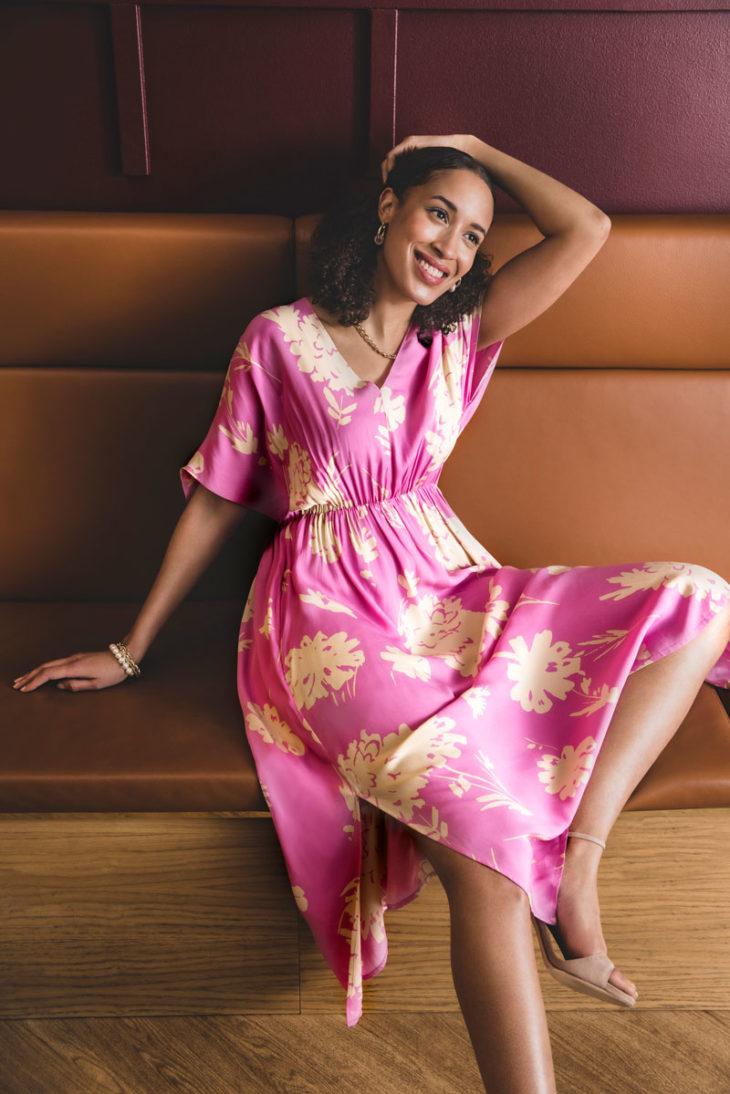 Nainen istuu sohvalla pinkissä kukkamekossaan.