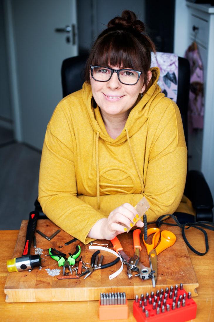 Yrittäjä Emilia Ikäheimonen istuu työvälineet edessään.