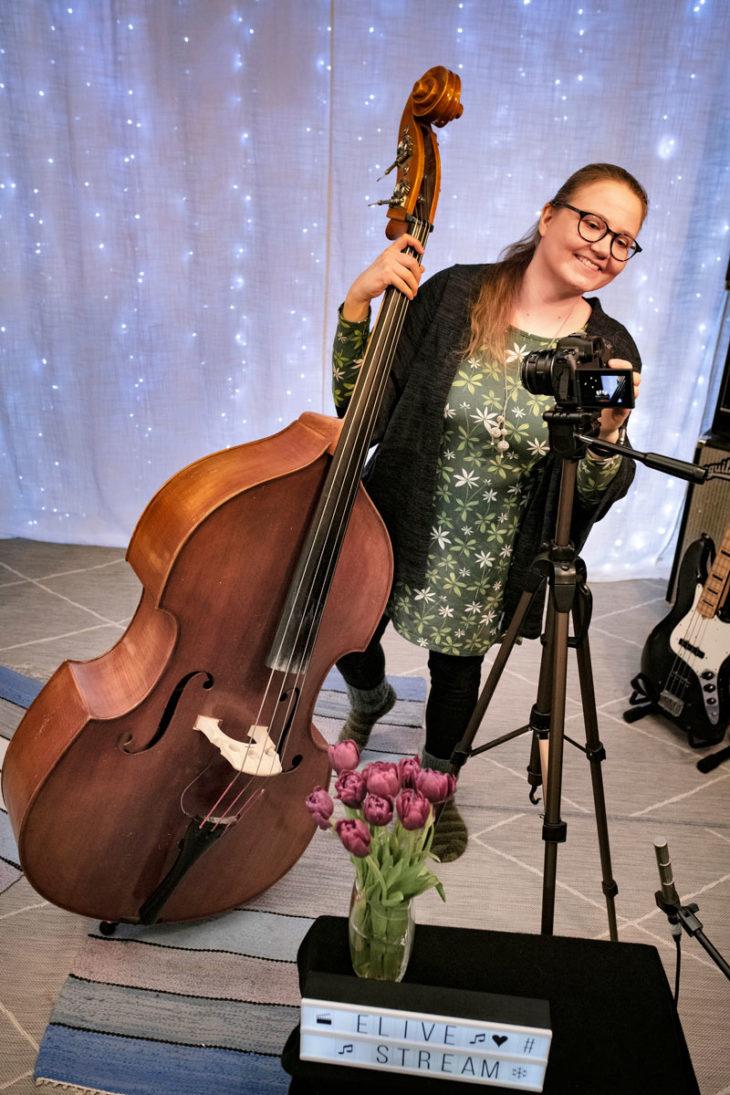 Jazzmuusikko Eevalotta Matikainen seisoo sellonsa vierellä.