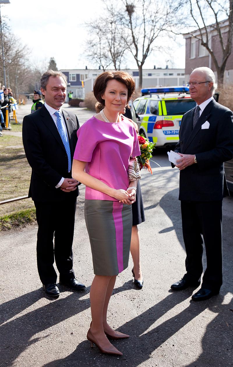 Jenni Haukio mekossa, jonka yläosa on vaaleanpunainen ja alaosa harmaa, jossa on vaaleanpunainen raita keskellä.