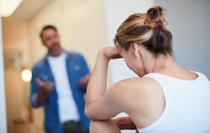 Nainen istuu etualalla pää käsiin painettuna, taustalla mieshenkilö selittelemässä. Jatkuva riitely parisuhteessa voi tuntua kehältä, josta ei pääse pois.
