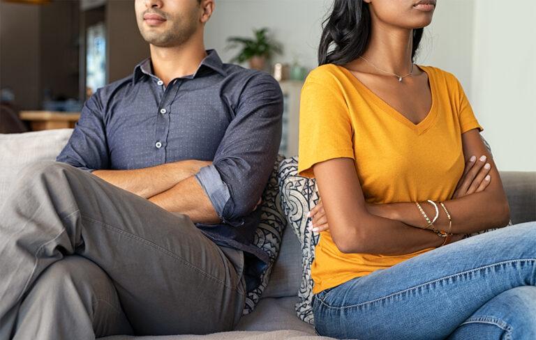 Pari istuu sohvalla kädet ristissä ja suuntaavat katseensa pois toisistaan.